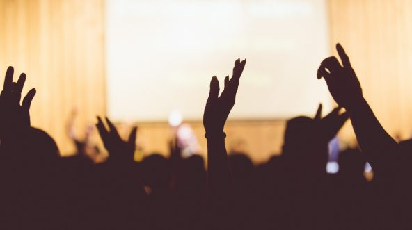 People's hands in the air praising God.