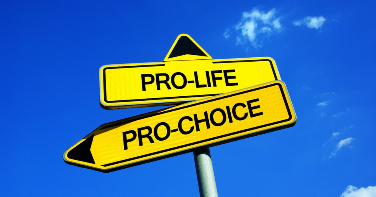 A fictional traffic sign with two options -- ethical dilemma of giving birth and forbidded termination or legal abortion. Freedom of mother vs value of human life