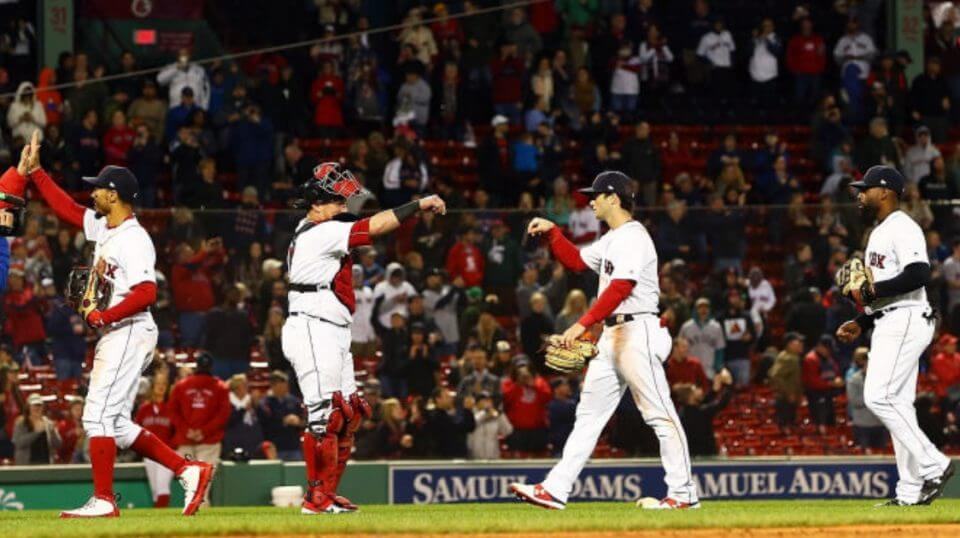 The Boston Red Sox high-five each other after defeating the Baltimore Orioles for their franchise-record 106th win Monday at Fenway Park.