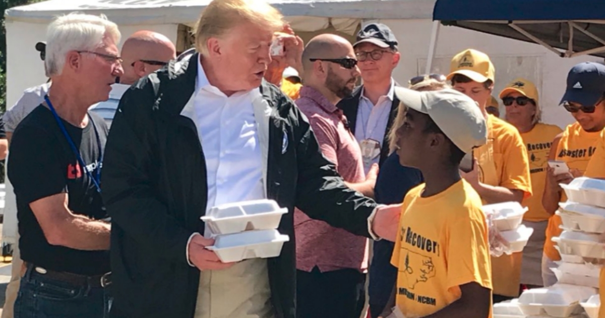 President Donald Trump visits with a young volunteer at Temple Baptist Church in New Bern, North Carolina as they hand out meals to survivors of Hurricane Florence.