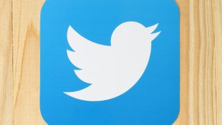 Twitter logo on a wood background.