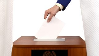 A paper ballot going into a ballot box.