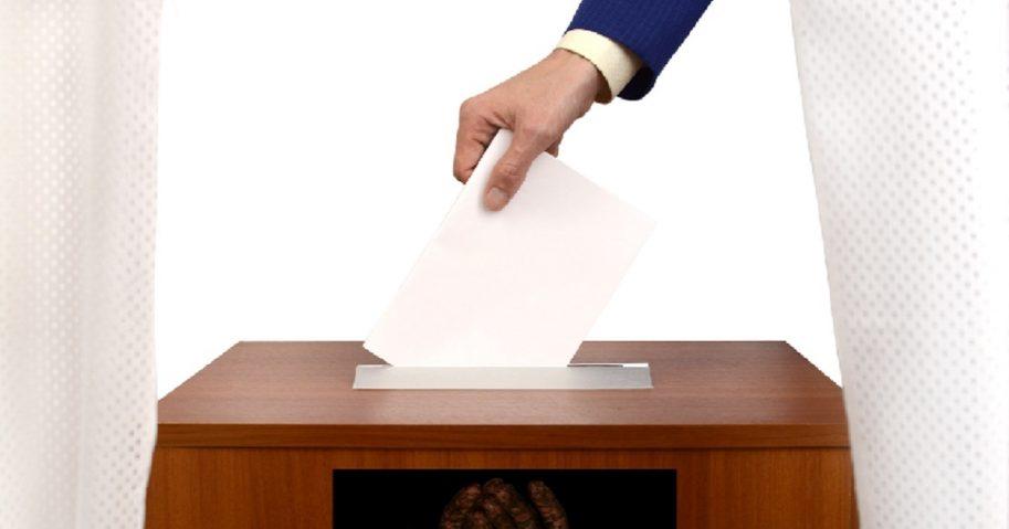 A paper ballot going into a ballot box.