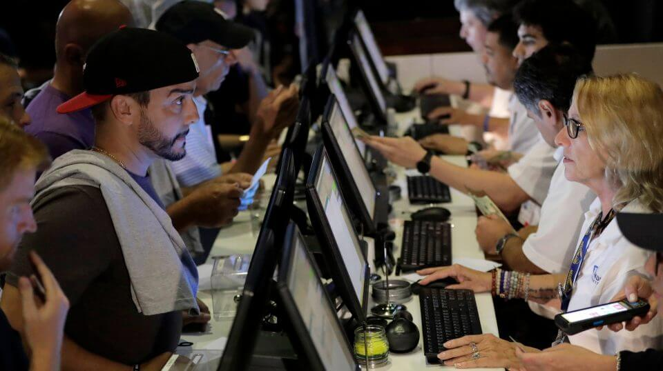 People, talk to tellers while placing bets at the Meadowlands Racetrack in East Rutherford, New Jersey, July 14.