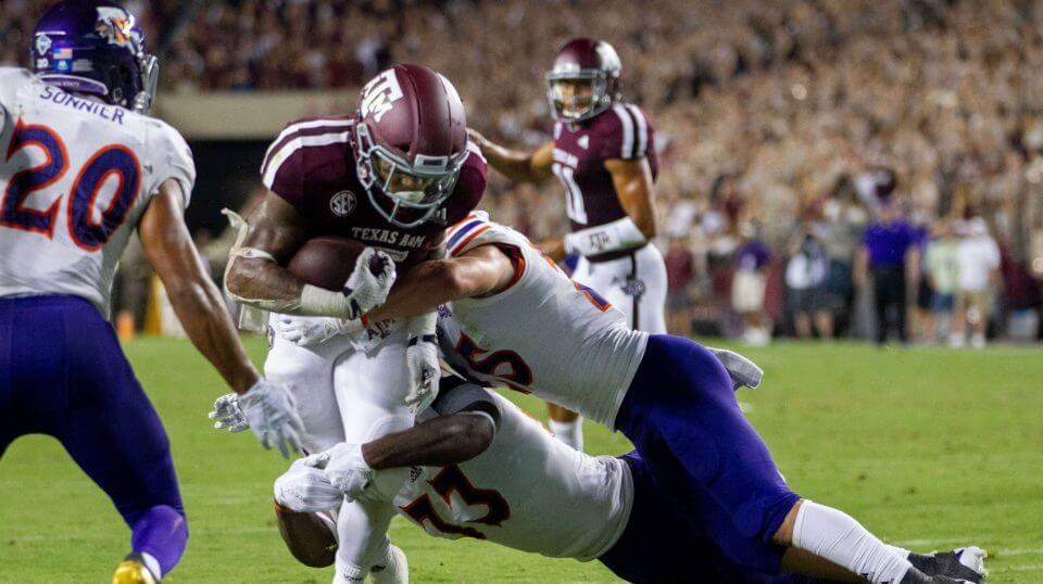 Texas A&M running back Trayveon Williams (5) fights off Northwestern State defenders on his way to a touchdown during the first half of NCAA college football game Thursday, Aug. 30, 2018, in College Station, Texas.