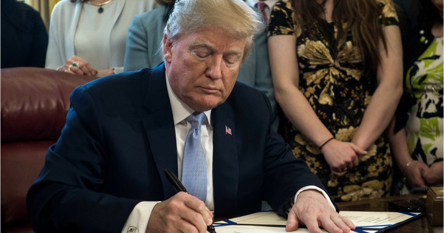 Donald Trump signs act at desk in Oval Office