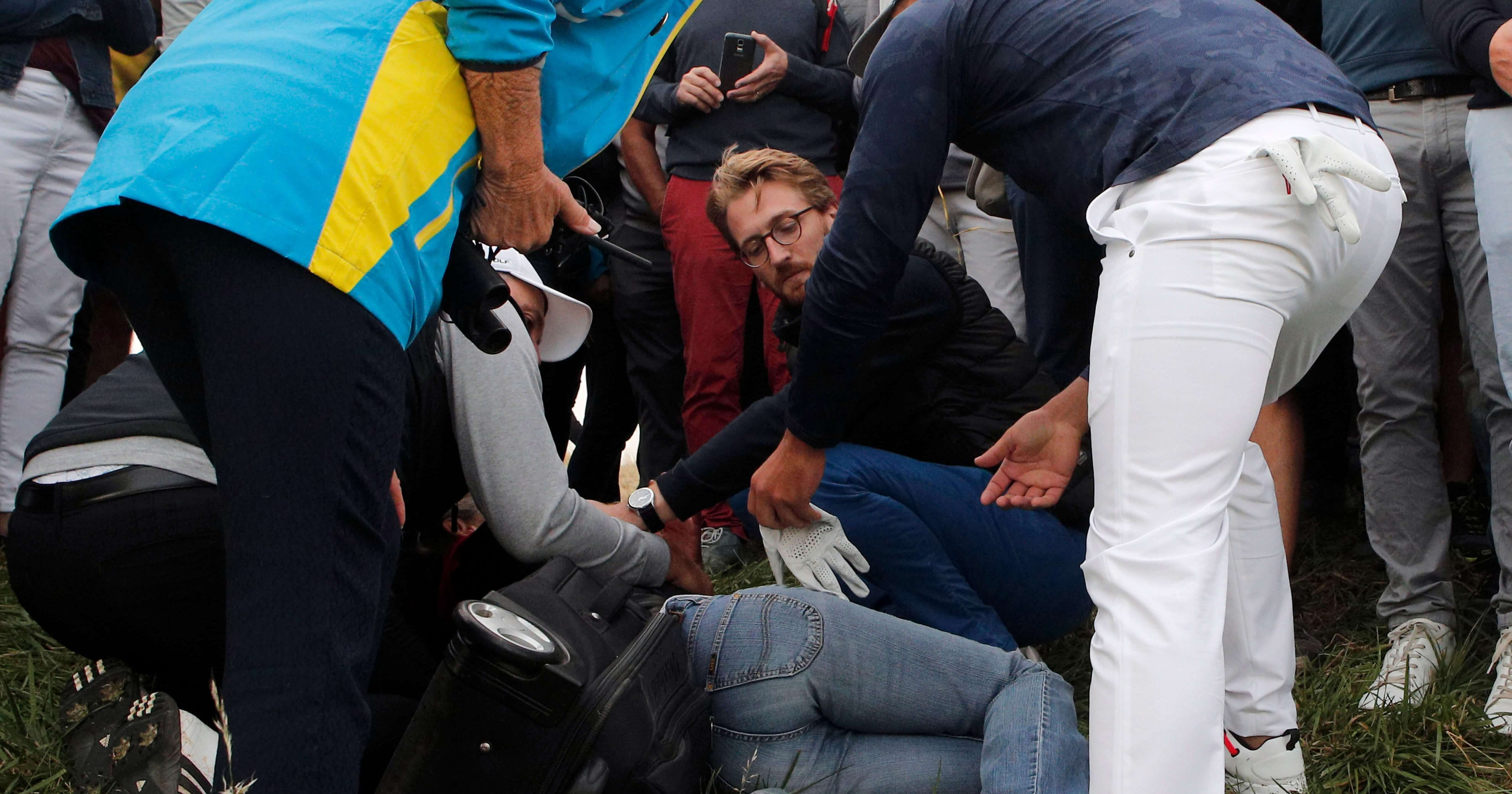 Brooks Koepka offers a golf glove to an unidentified woman Friday after his ball hit her on the 6th hole during a fourball match on the opening day of the 42nd Ryder Cup at Le Golf National in Saint-Quentin-en-Yvelines, outside Paris.