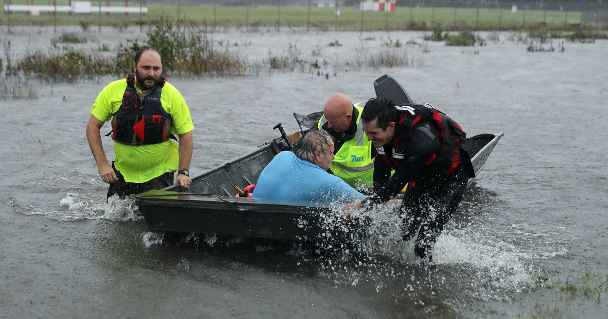 Volunteers from the Civilian Crisis Response Team rescue a man with chest pains from his flooded home