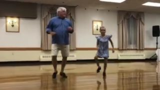 A grandfather dancing with his granddaughter.