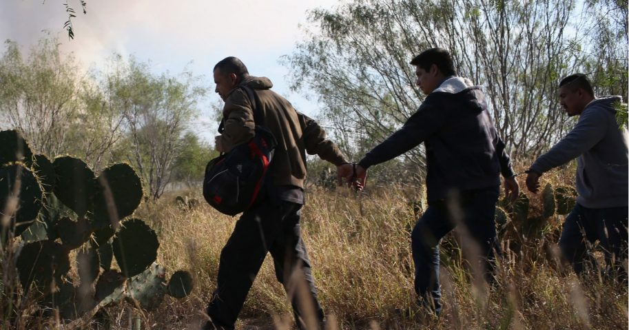 Immigrants walk handcuffed after illegally crossing the U.S.-Mexico border