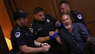 A protester is led away by police after disrupting the second day of the confirmation hearing for Supreme Court nominee Judge Brett Kavanaugh