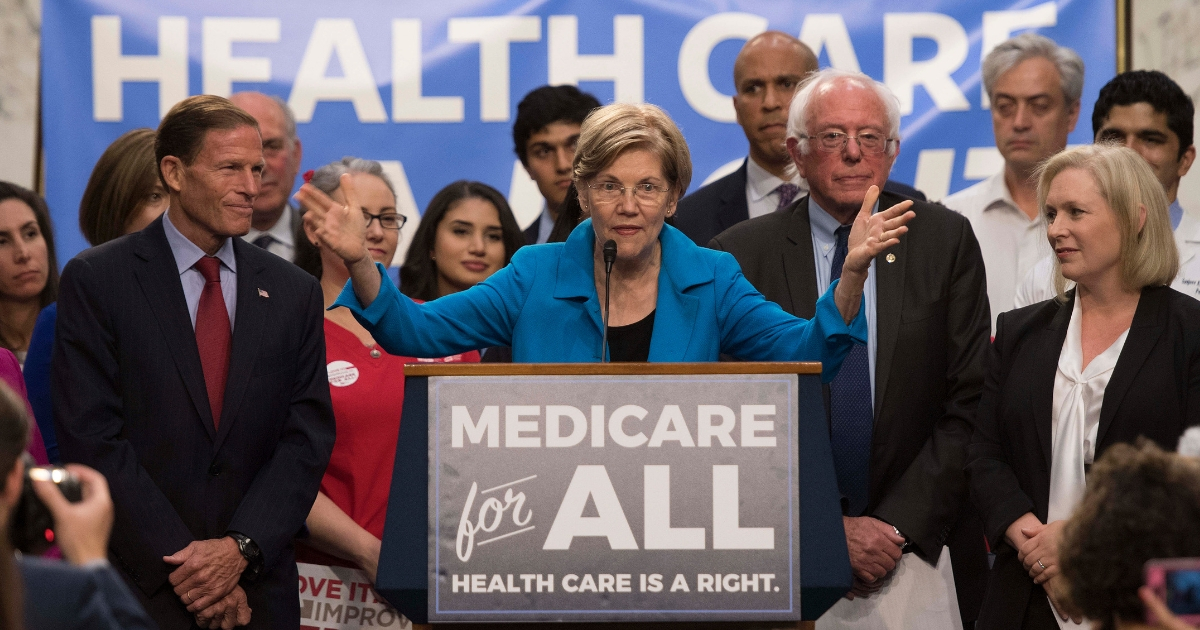 US Senator Elizabeth Warren (C), Democrat from Massachusetts, speaks with US Senator Bernie Sanders (2nd R), Independent from Vermont, as they discusses Medicare for All legislation on Capitol Hill in Washington, DC