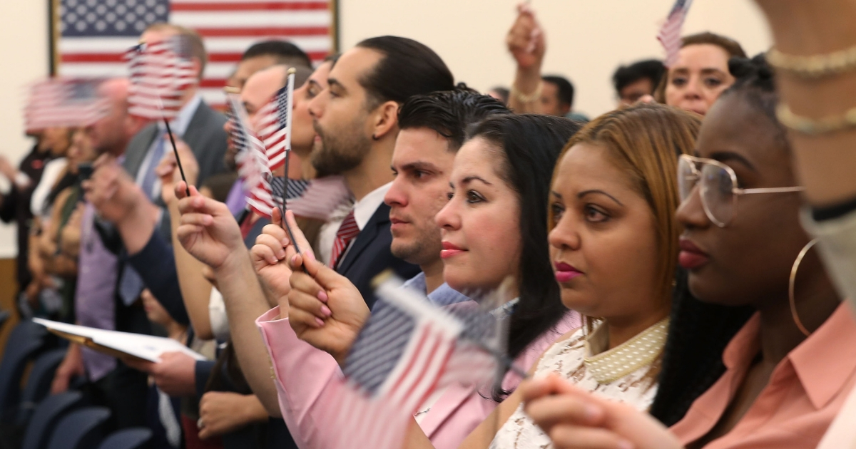 People participate in a ceremony to become American citizens during a U.S. Citizenship & Immigration Services naturalization ceremony at the Miami Field Office on Aug. 17, 2018, in Miami, Florida.