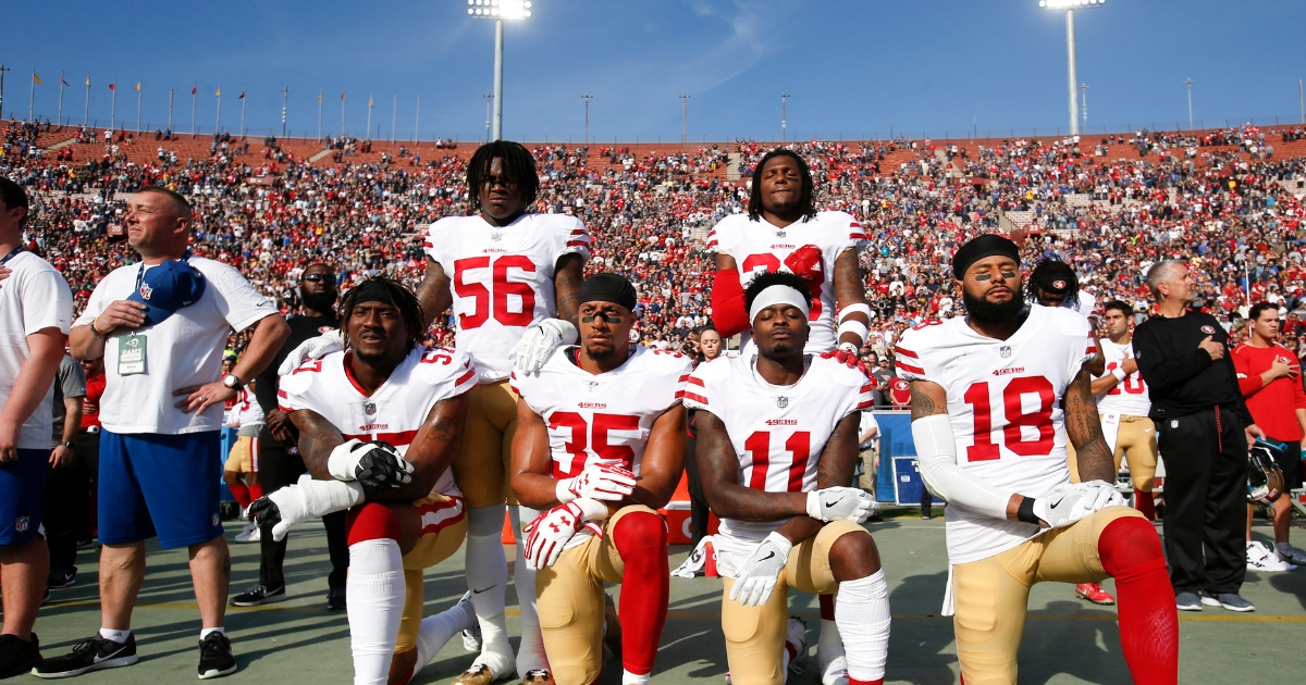 Eli Harold #57, Eric Reid #35, Marquise Goodwin #11 and Louis Murphy #18 of the San Francisco 49ers kneel during the anthem