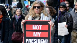 Woman carrying 'not my president' sign.