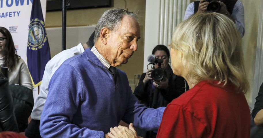 Former New York Mayor Michael Bloomberg talks to a woman