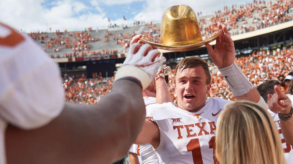 Texas quarterback Sam Ehlinger (11) holds the Golden Hat as he celebrates with teammates after defeating Oklahoma 48-45 Saturday at the Cotton Bowl in Dallas.