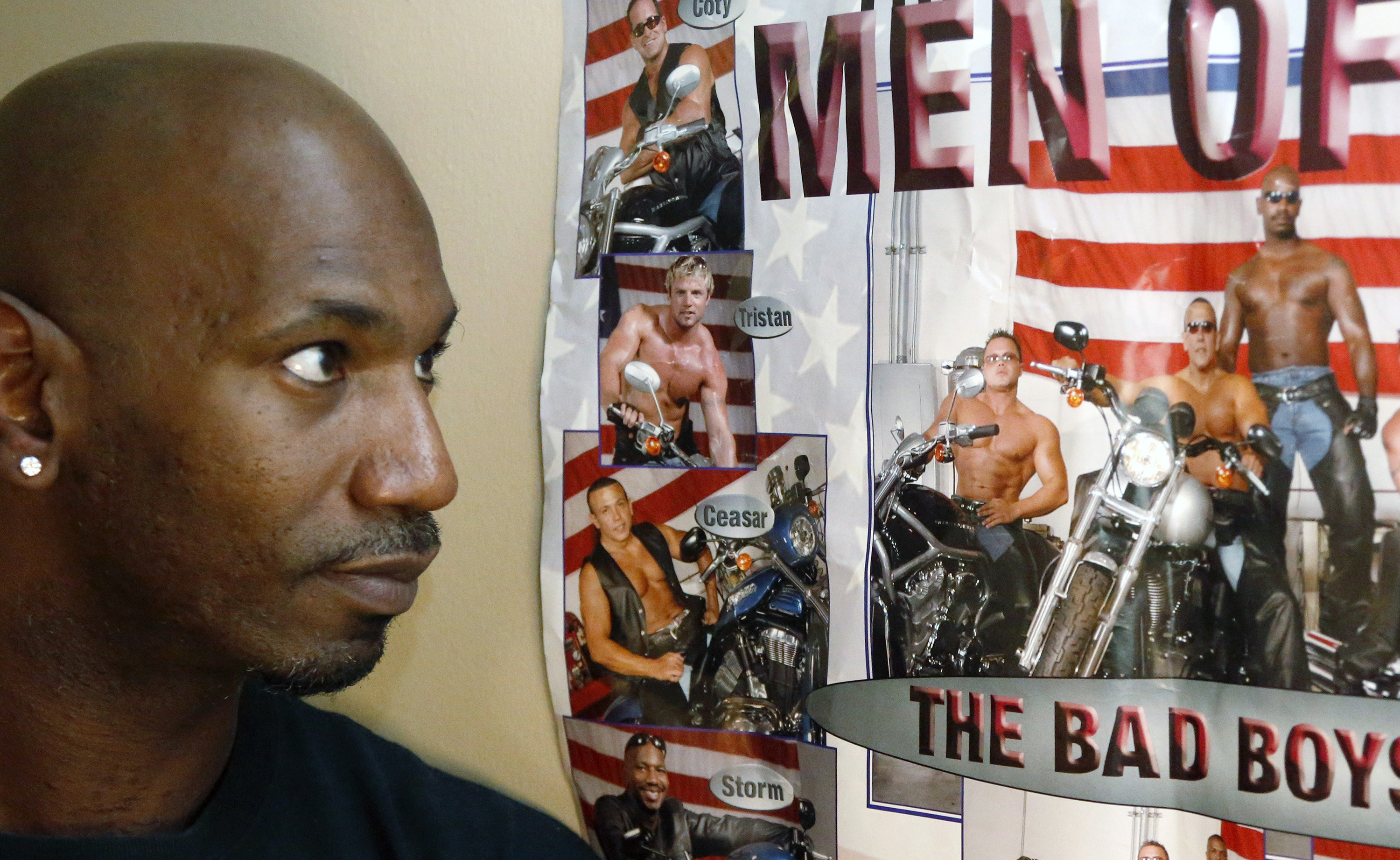 Former male dancer David Crosby, left, looks at a poster showing Cesar Sayoc