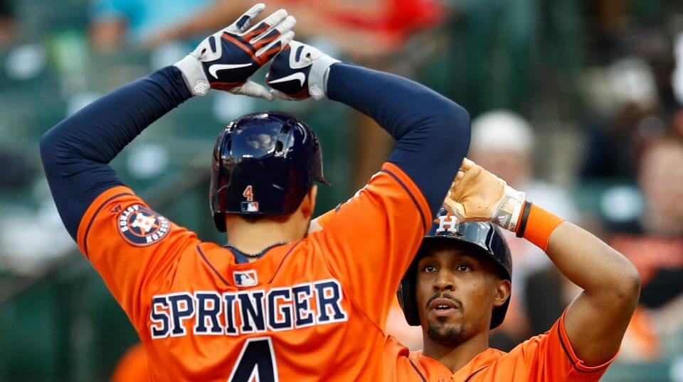 Houston Astros' Tony Kemp, right, high-fives teammate George Springer after scoring on Springer's two-run home run in the sixth inning of the first game of a doubleheader against the Baltimore Orioles on Saturday.