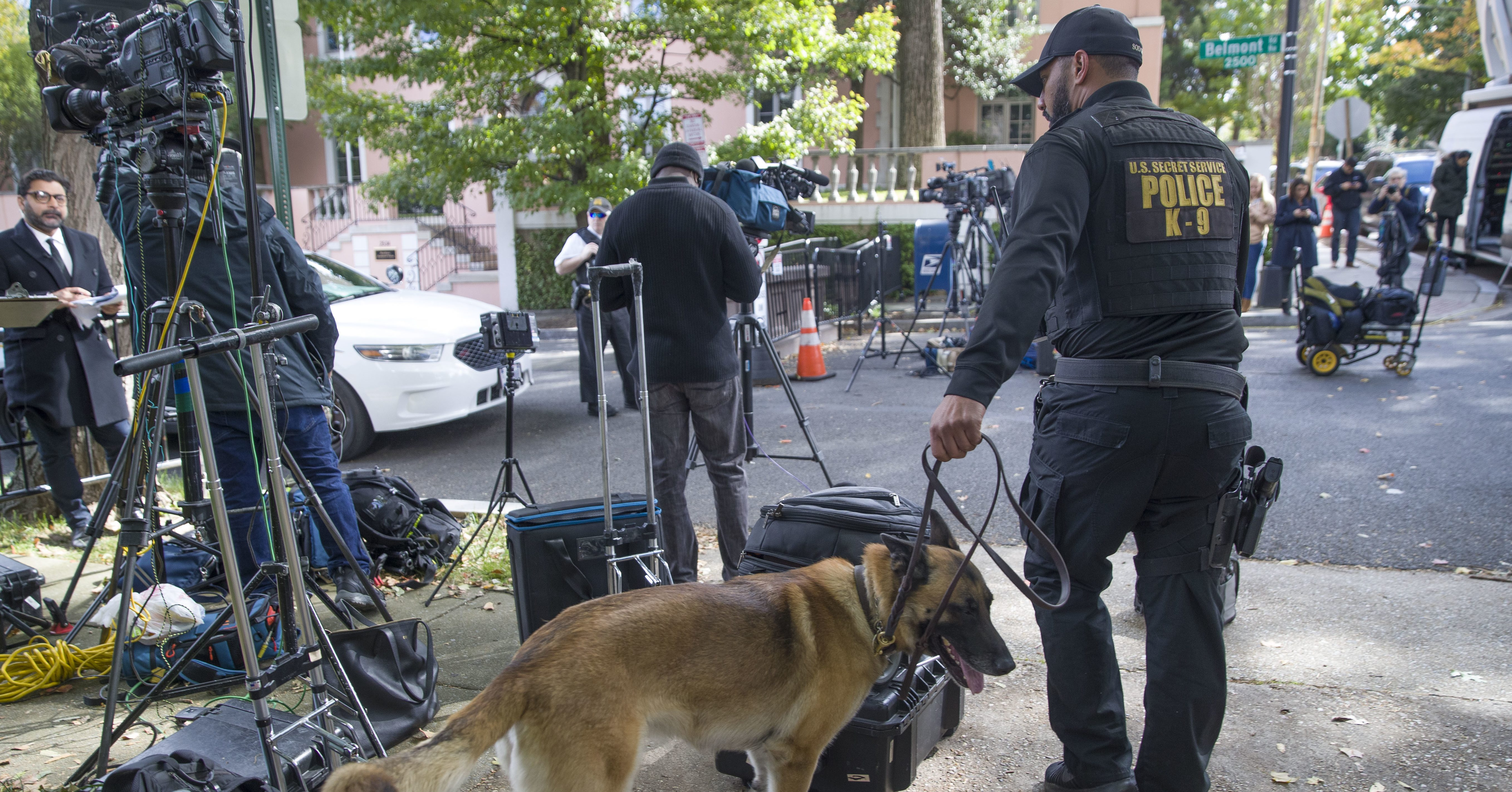 An officer with the Uniform Division of the United States Secret Service uses his dog to search a checkpoint