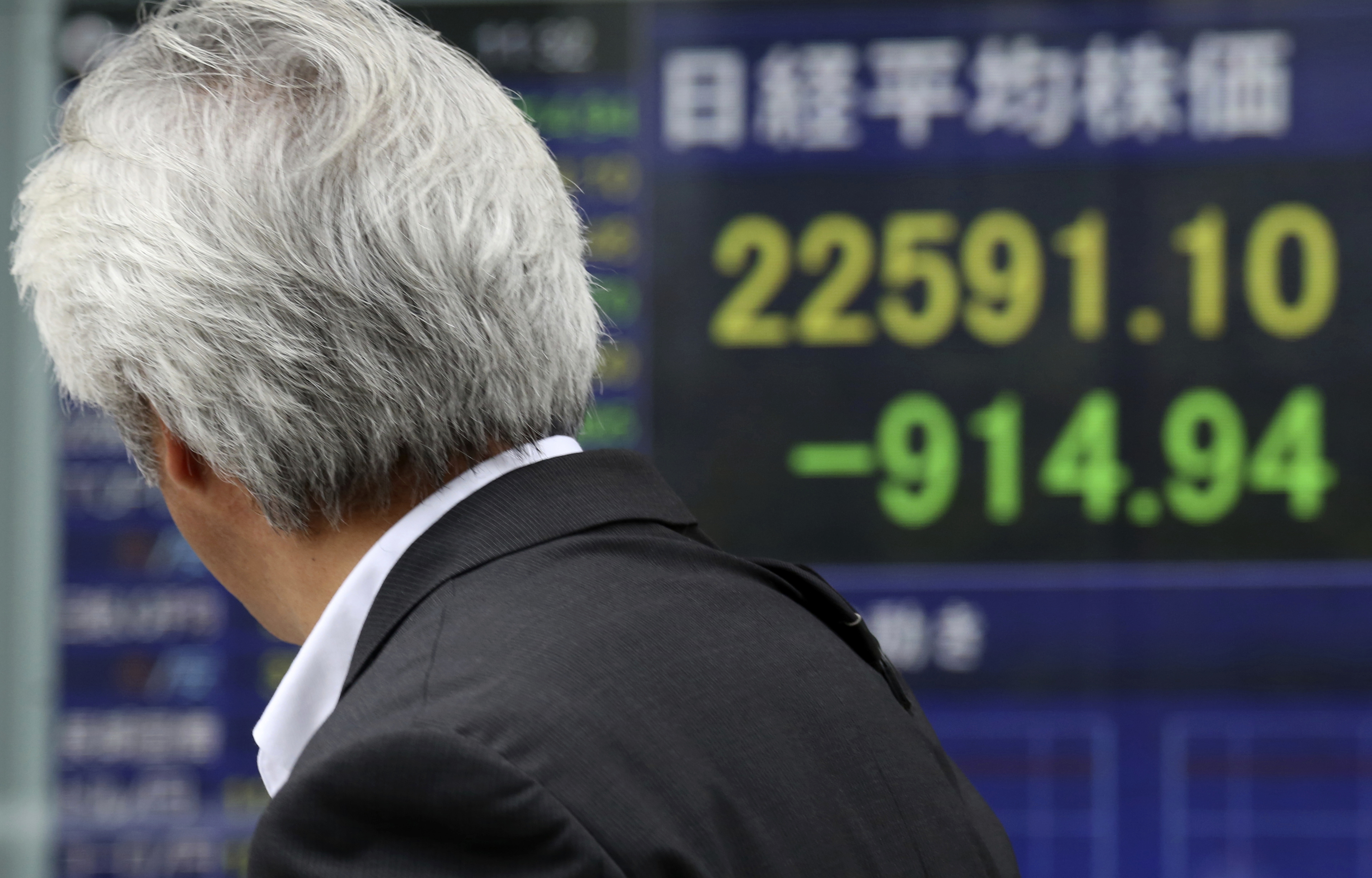 A man looks at an electronic stock board of a securities firm in Tokyo on Thursday. Asian markets tumbled a day after Wall Street slumped on a heavy selling of technology and internet stocks. Japan's benchmark fell by an unusually wide margin of 3.9 percent.
