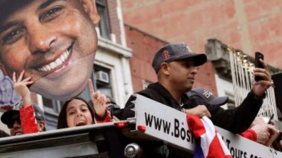 Boston Red Sox manager Alex Cora takes a photo as his daughter Camila, left, holds a cutout photo of him during a parade to celebrate the team's World Series championship Wednesday in Boston.