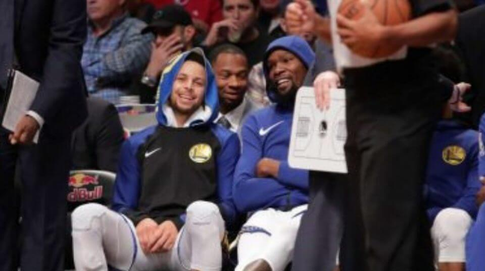 Stephen Curry, left, and Kevin Durant smile during the first half of Golden State's game at Brooklyn on Sunday.