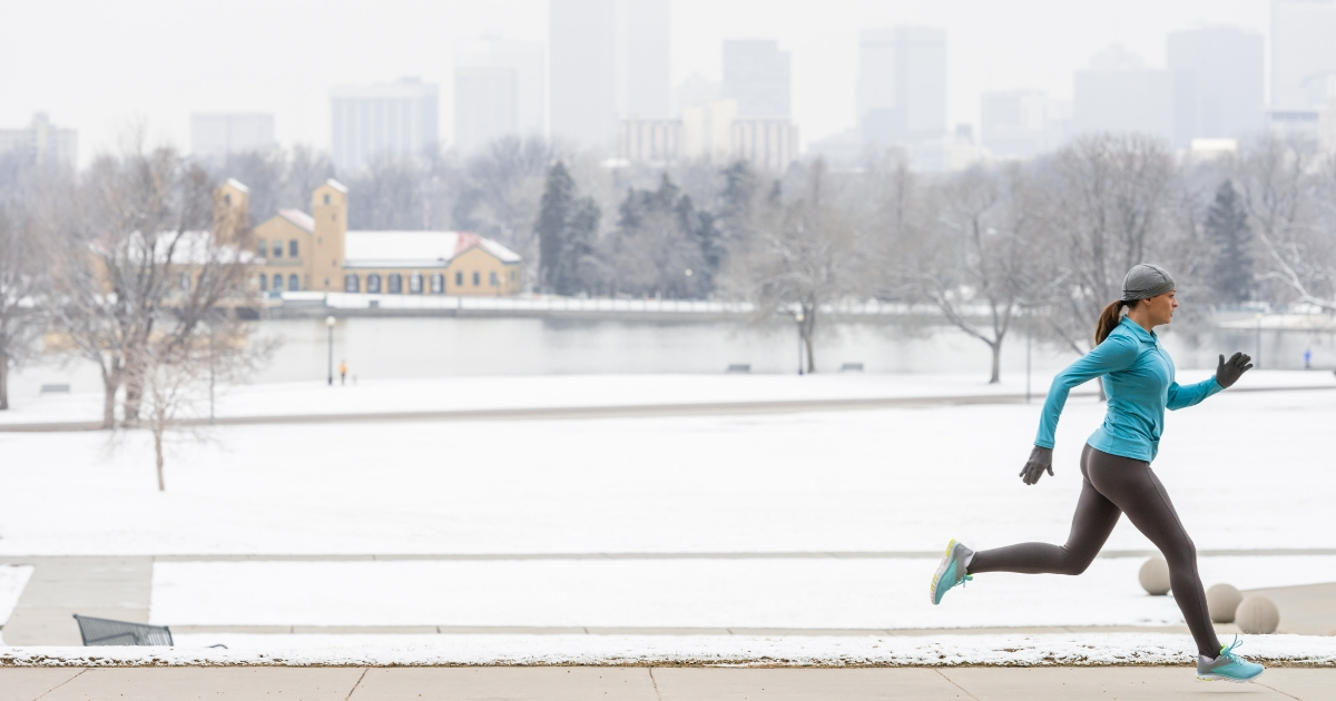 Young Woman Running in Snowy Park with Denver Skyline in background