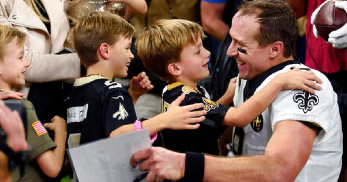 New Orleans Saints quarterback Drew Brees greets his family after breaking the NFL all-time passing yards record in the first half of Monday night's game against the Washington Redskins in New Orleans.