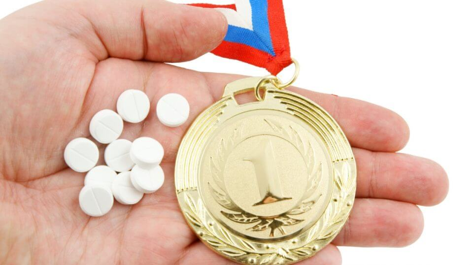 Pills are held next to a gold medal