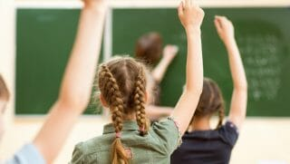 Children raise their hands in a school classroom