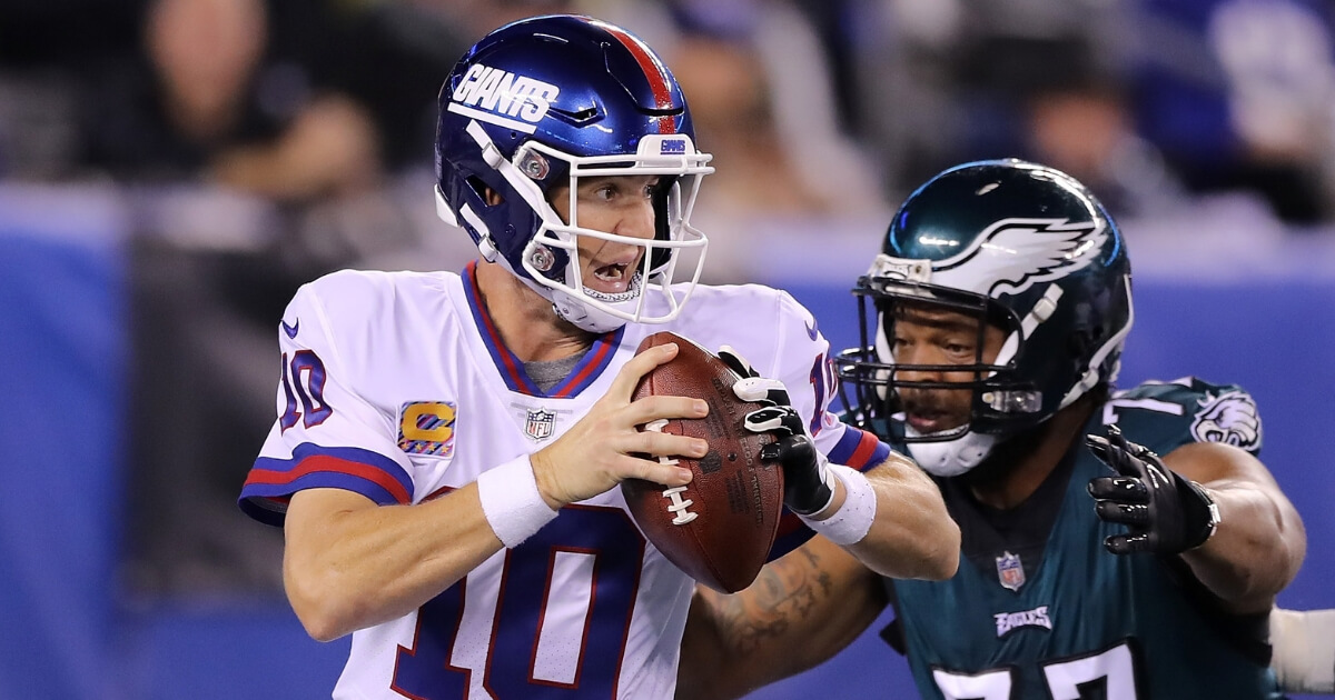 Eli Manning of the New York Giants scrambles before fumbling the ball from a hit by Michael Bennett of the Philadelphia Eagles during the first quarter of their game Thursday night at MetLife Stadium in East Rutherford, New Jersey.