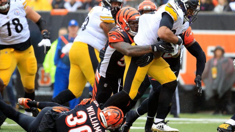 Vontaze Burfict #55 of the Cincinnati Bengals and Shawn Williams #36 combine to tackle James Conner #30 of the Pittsburgh Steelers during the second quarter at Paul Brown Stadium on October 14, 2018.