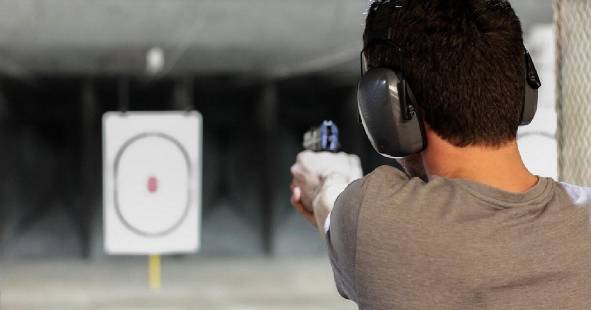 Man with handgun at shooting range.