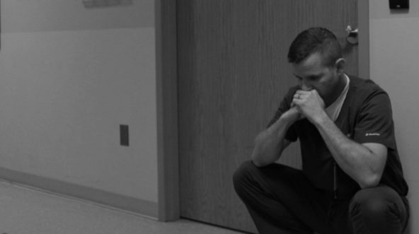 Doctor crouching down outside Trauma Family Waiting Room at hospital