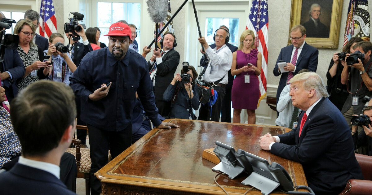 Rapper Kanye West stands up as he speaks during a meeting with U.S. President Donald Trump