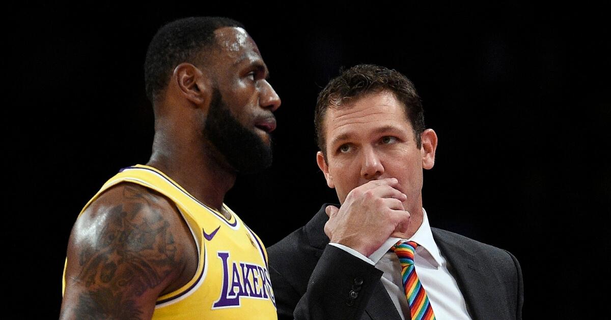 Head coach Luke Walton of the Los Angeles talks with LeBron James.