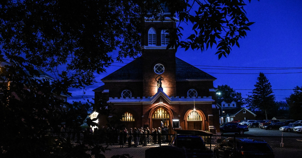 Mourners line up in front of St. Stanislaus Roman Catholic Church