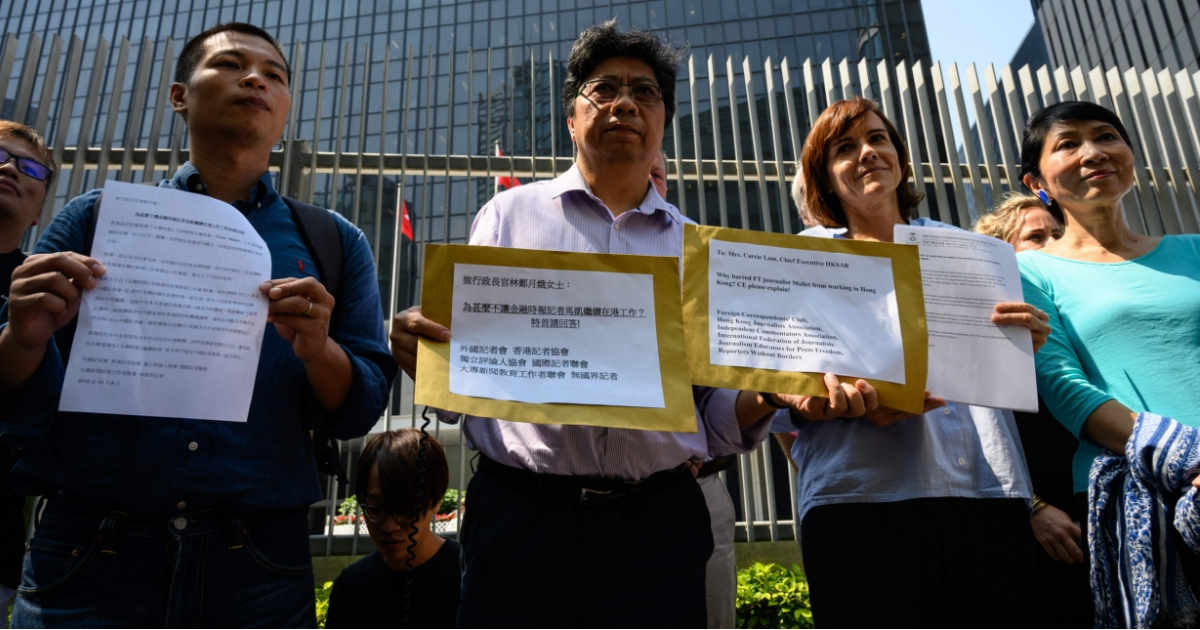 Chris Yeung, center, chairman of the Hong Kong Journalists Association, leads a rally for Financial Times journalist Victor Mallet outside the government headquarters in Hong Kong on Monday.