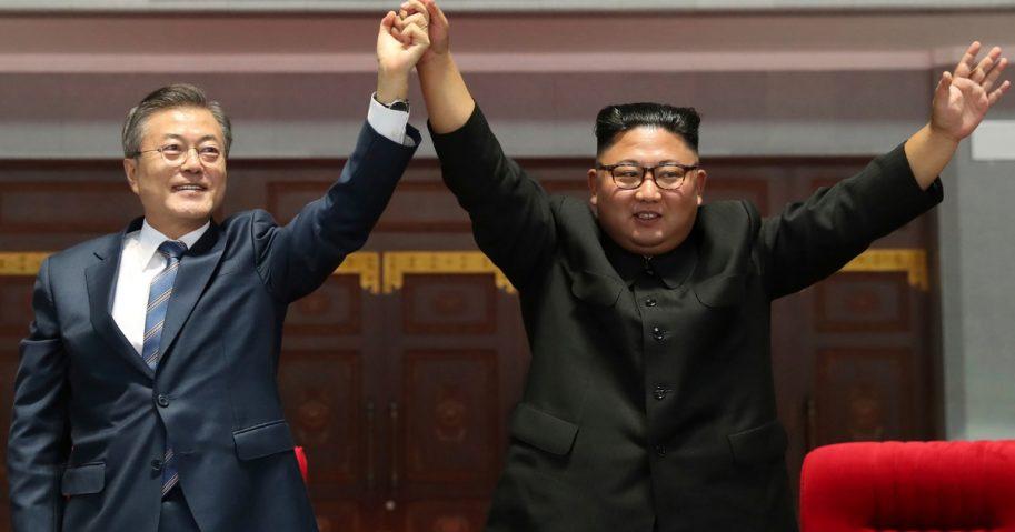 South Korean President Moon Jae-in and North Korean leader Kim Jong Un hold and raise their hands