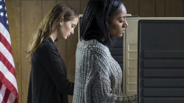 Two women, one white and one black, vote at voting booths