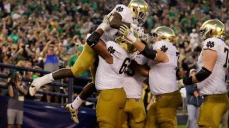 Notre Dame running back Dexter Williams is lifted by teammate long snapper Michael Vinson after scoring a touchdown during Saturday's game against Navy