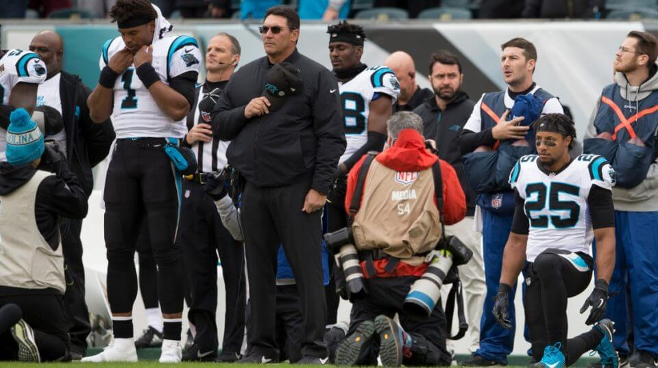 Cam Newton, left,and head coach Ron Rivera of the Carolina Panthers stand for the national anthem while Eric Reid takes a knee prior to their game against the Philadelphia Eagles at Lincoln Financial Field on Sunday.