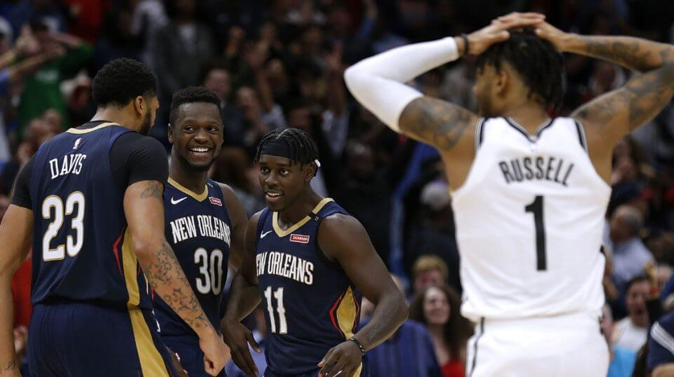 The Nets' D'Angelo Russell, right, watches while Jrue Holiday (11), Anthony Davis (23) and Julius Randle (30) of the Pelicans celebrate their improbably comeback victory Friday at the Smoothie King Center in New Orleans.