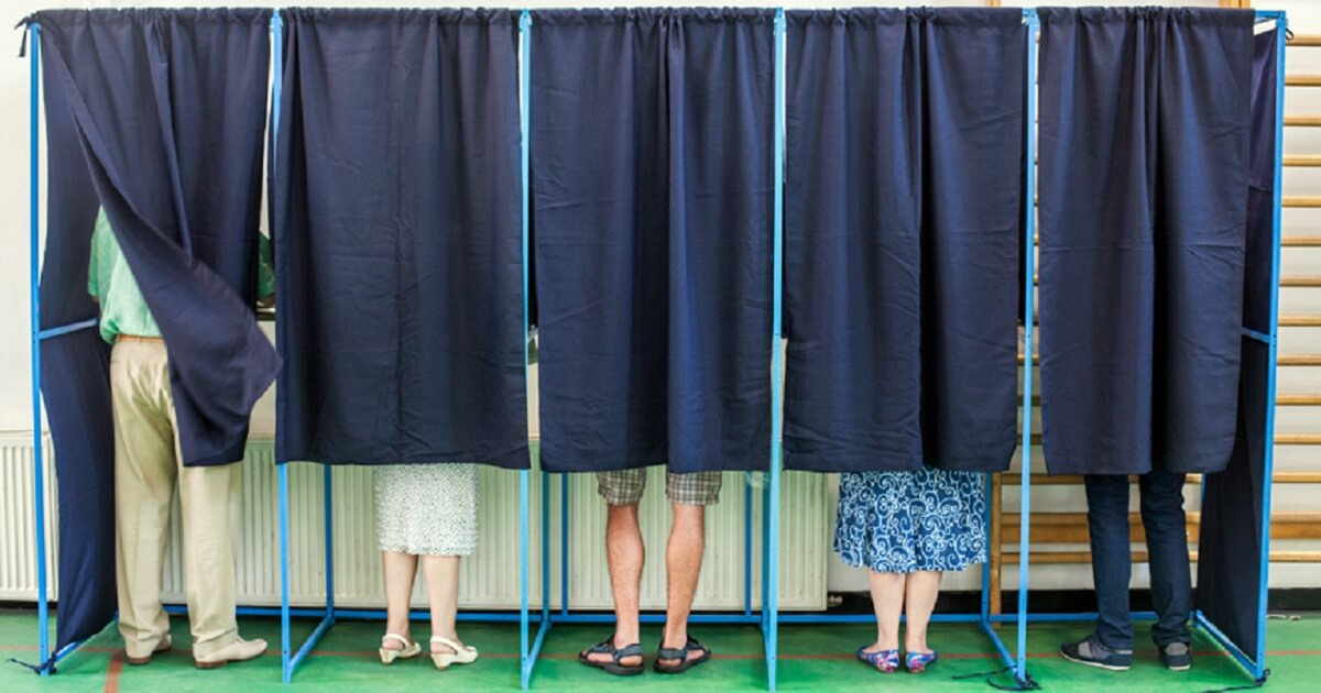 Exterior shot of voters inside polling places with curtains pulled.