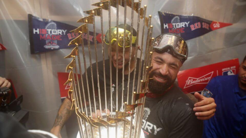 Catcher Sandy Leon of the Boston Red Sox celebrates with the World Series trophy