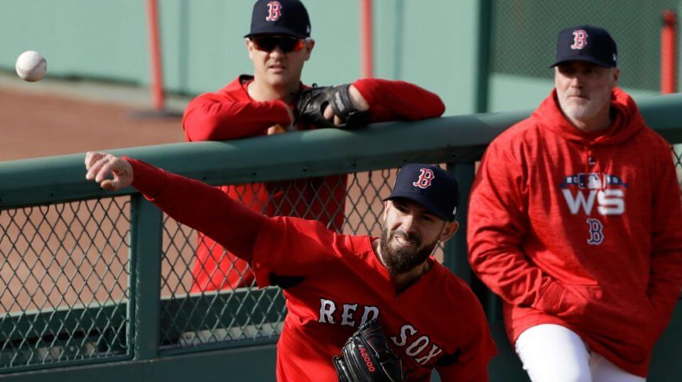 Boston Red Sox pitcher Rick Porcello, center, throws in the bullpen during a team workout Monday.
