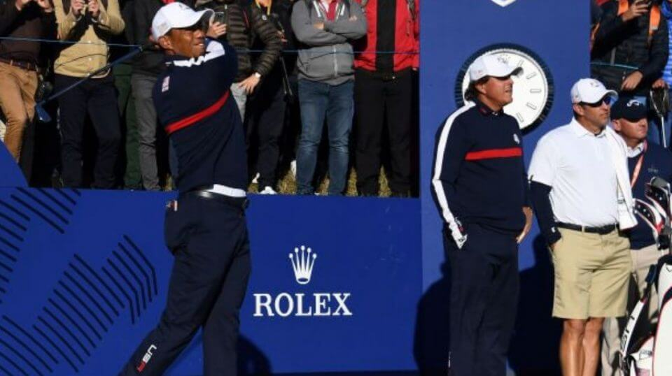 Tiger Woods, left, tees off as teammate Phil Mickelson looks on during a practice session ahead of the 42nd Ryder Cup