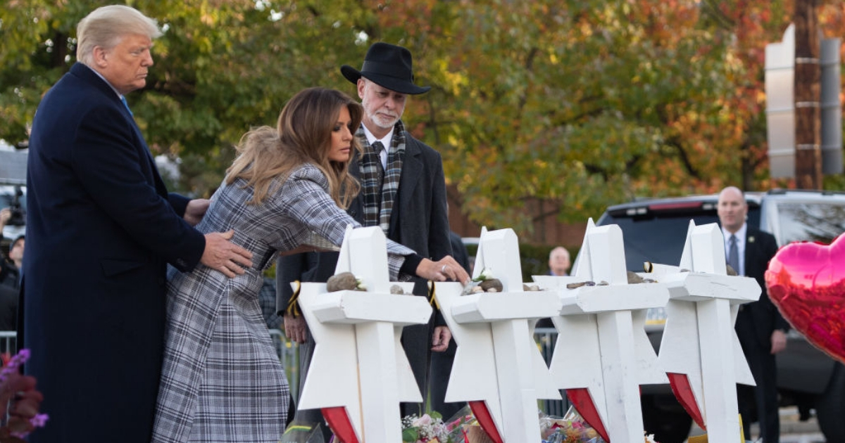President Donald Trump and first lady Melania Trump, alongside Rabbi Jeffrey Myers, place stones and flowers on a memorial Tuesday as they pay their respects at the Tree of Life Synagogue following last weekend's shooting in Pittsburgh.