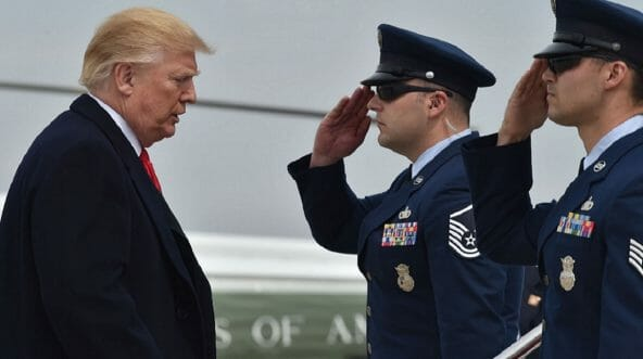 President Donald Trump is saluted as he transfers from Marine One to Air Force One at Andrews Air Force Base in Maryland in March.
